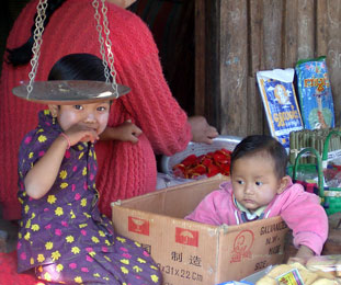 Lady with baby in a cardboard box in Yunan, China.